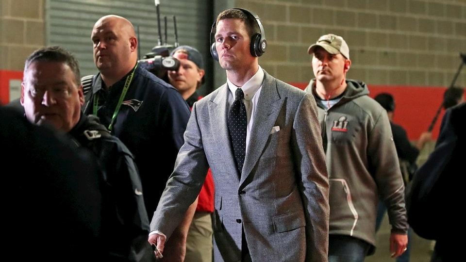 Tom Brady de terno e fone de ouvido em ambiente esportivo