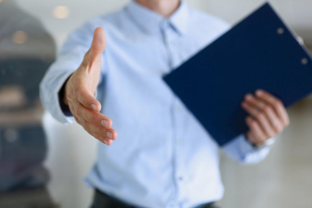Homem de negócios de roupa social segurando pasta e estendendo a mão para fechar negócio